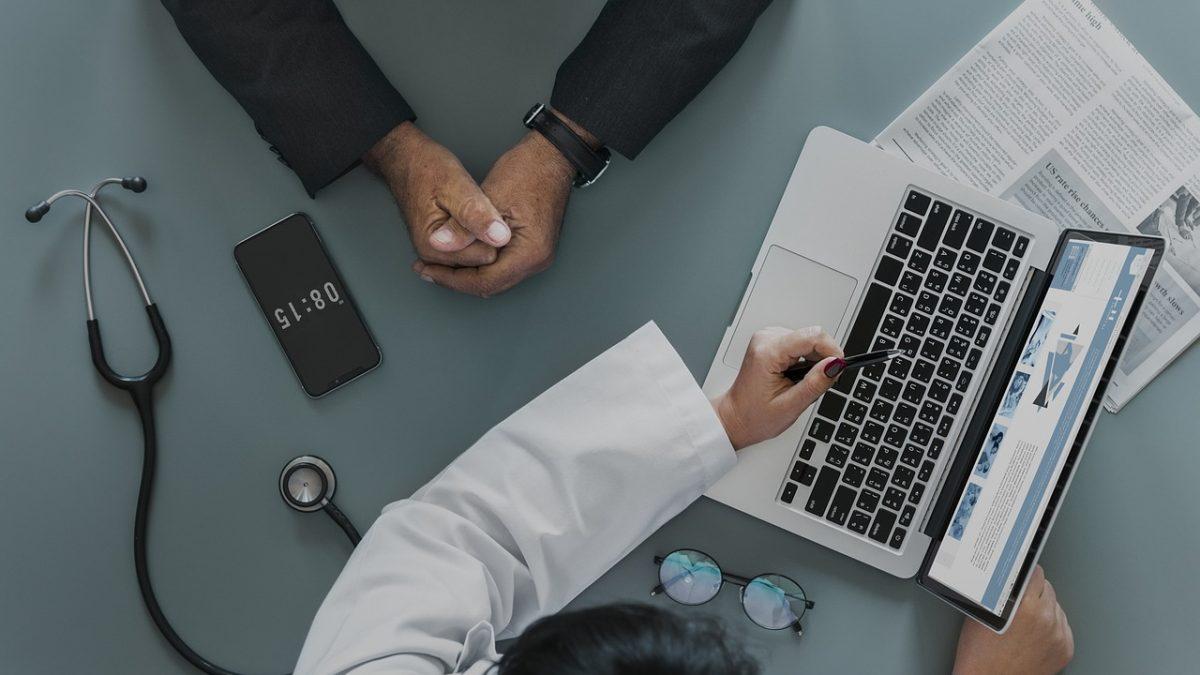 pedir cita medico parla madrid, medico con ordenador explicando a paciente
