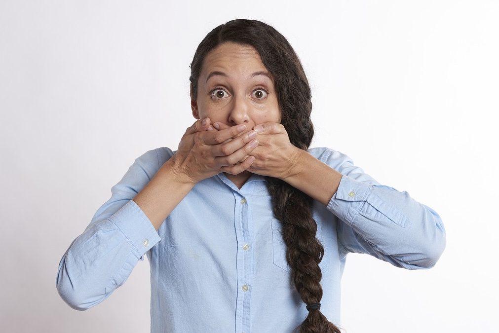 Habitos cotidianos que dañan nuestros dientes, mujer tapándose la boca
