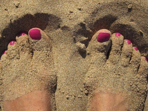 cuida tus pies en verano, consejos de tu podologo de parla, pies en arena de playa